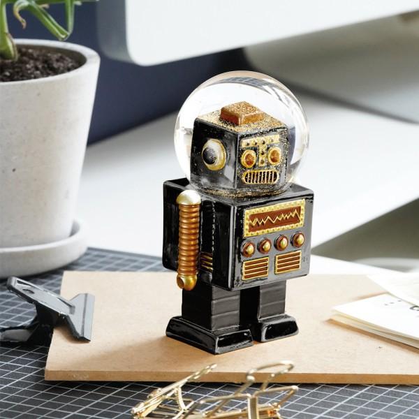 Boule à neige en forme de robot noir, de la marque Donkey. Le robot est mis en situation comme presse papier.
