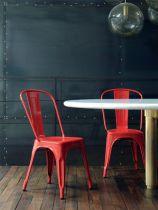Deux chaises A de la marque Tolix mis en situation autour d'une table, de coloris rouge piment